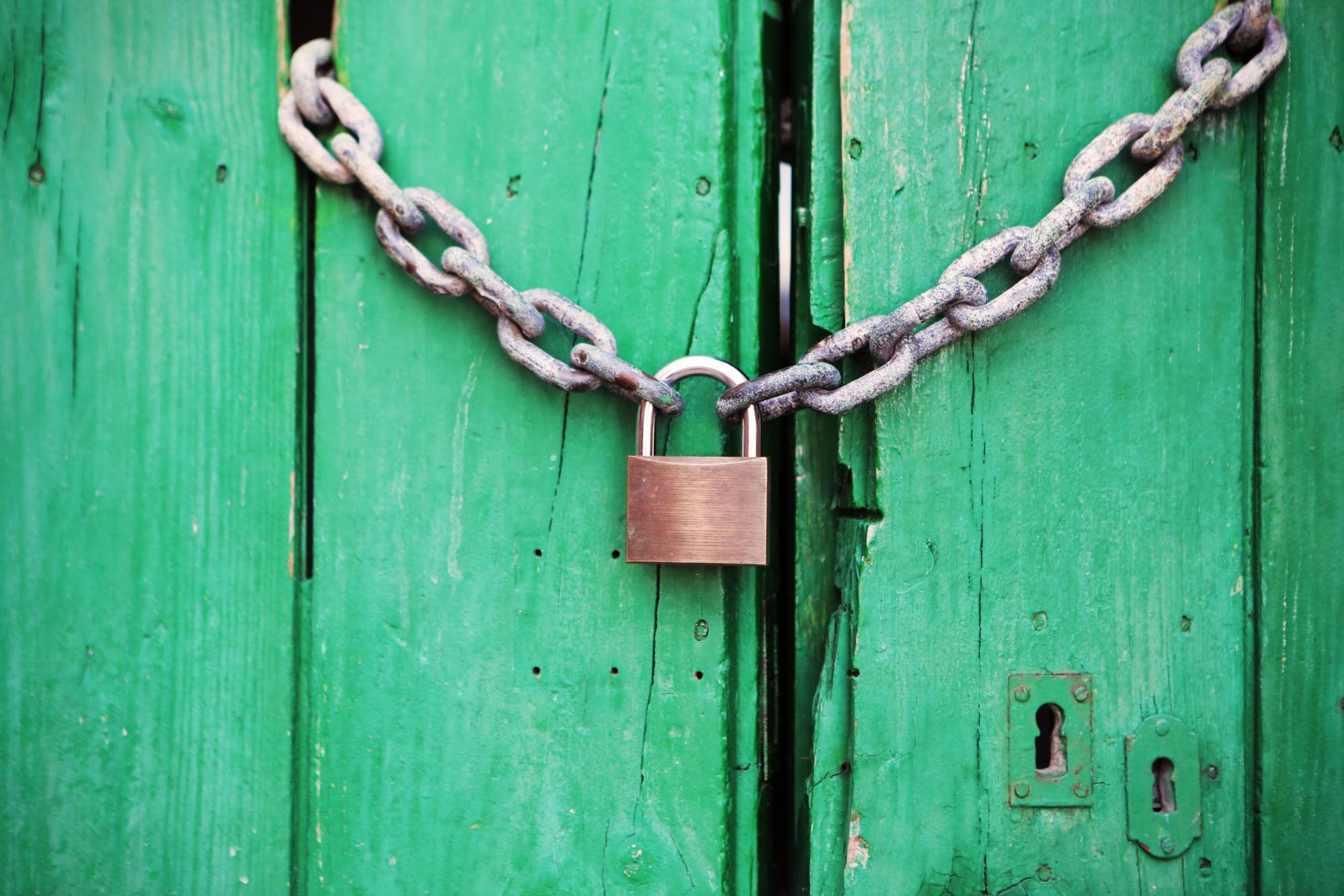 A padlock with a chain link security green wooden doors.